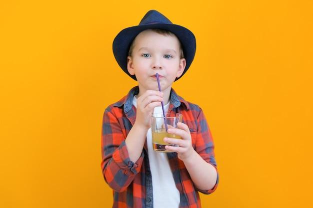 Junge mit hut trinkt saft mit einem strohhalm. entspannendes konzept. gelber hintergrund platz für ihren text. attrappe, lehrmodell, simulation