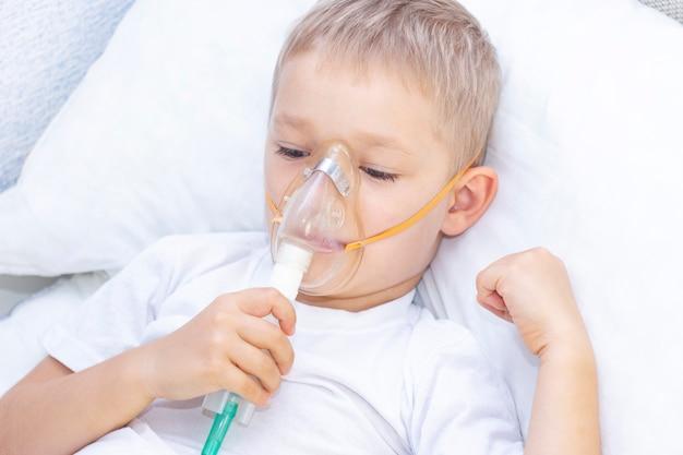 Junge mit inhalatormaske. atemprobleme bei asthma. junge mit inhalatormaske liegt im bett und atmet adrenalin.