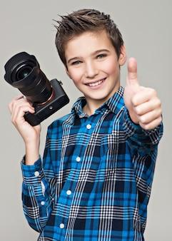 Junge mit kamera, die bilder macht. glücklicher spaßjunge mit dslr-kamera, die den daumen oben zeigt