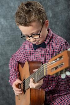 Junge mit kariertem hemd, das auf akustischer gitarre spielt