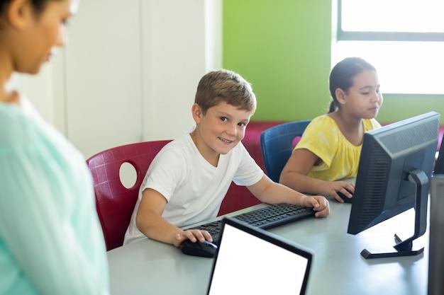 Junge mit klassenkamerad und lehrer, der computer benutzt