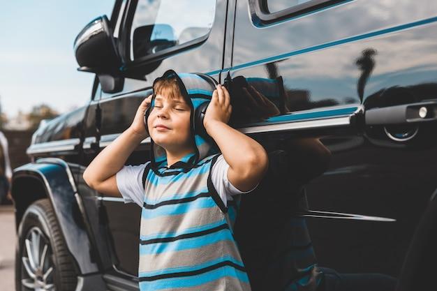 Junge mit kopfhörern, die musik neben dem auto hören