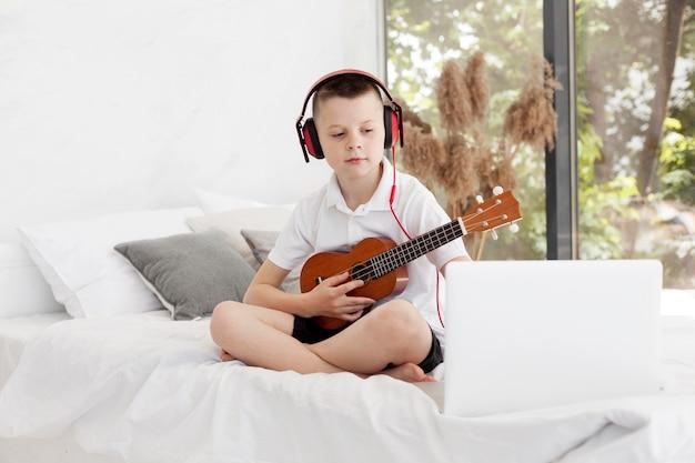 Junge mit kopfhörern, die ukulele spielen