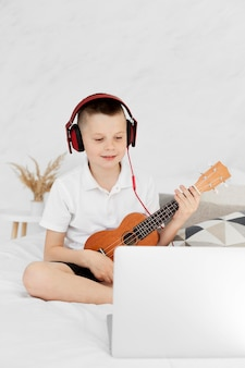Junge mit kopfhörern, die ukulele-vorderansicht spielen