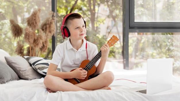 Junge mit kopfhörern spielt ukulele long shot