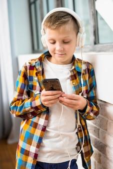 Junge mit kopfhörern unter verwendung des smartphone