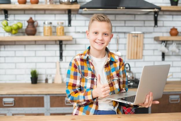 Junge mit laptop in der küche