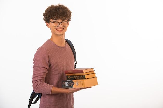 Junge mit lockigem haar in einer optischen brille, die schulbücher hält, lächelt und zuversichtlich aussieht.