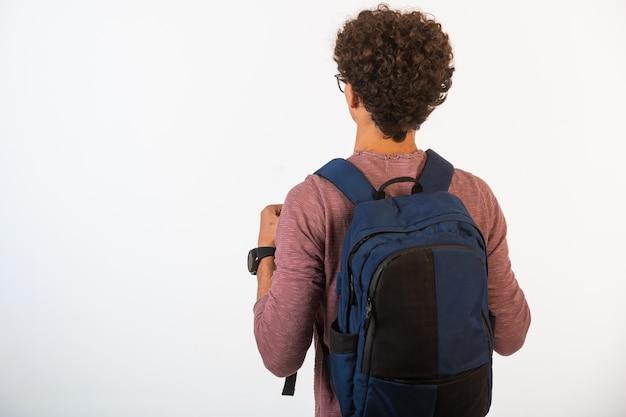 Junge mit lockigem haar in einer optischen brille, die seinen rucksack hält.