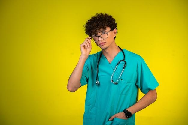 Junge mit lockigem haar in medizinischer uniform mit stethoskop