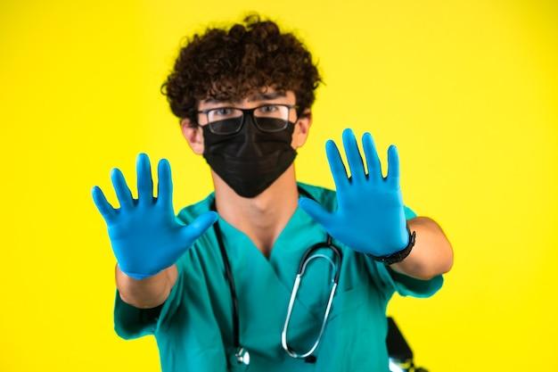 Junge mit lockigem haar in medizinischer uniform und gesichtsmaske, die hygiene auf gelbem hintergrund demonstriert