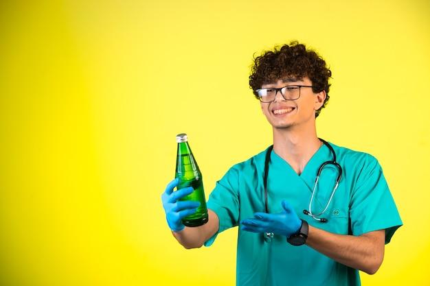 Junge mit lockigem haar in medizinischer uniform und handmasken, die eine flasche flüssigkeit zeigen und lächeln.