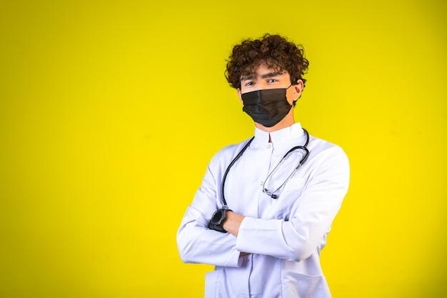 Junge mit lockigem haar in weißer medizinischer uniform mit stethoskop, das gesichtsmaske trägt