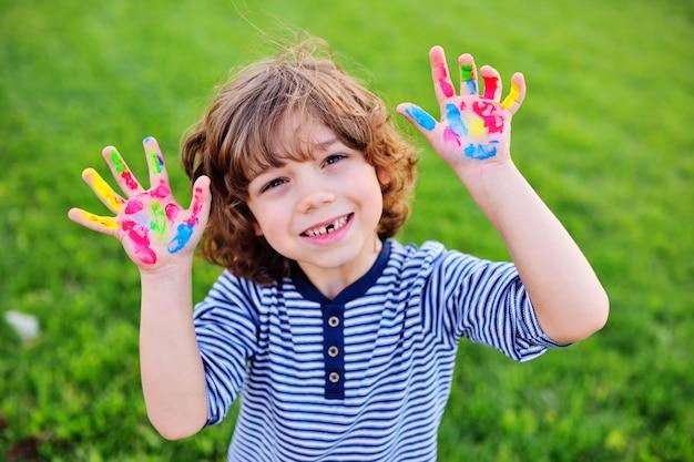 Junge mit lockigem haar ohne vorderem milchzahn zeigt die hände, die mit mehrfarbigen fingerfarben und lächeln schmutzig sind.