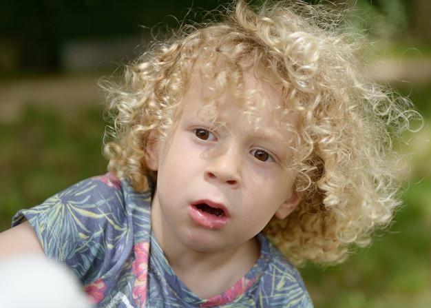 Junge mit lockigen blonden haaren, draußen