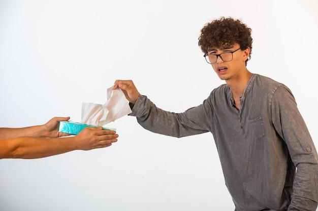 Junge mit lockigen haaren und in optischen gläsern, die ein taschentuch zur händedesinfektion nehmen.