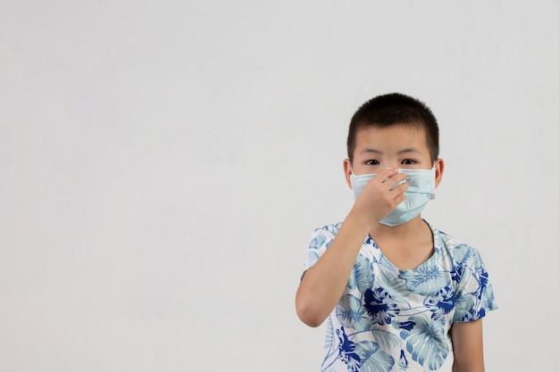 Junge mit maske, die auf weißem hintergrund aufwirft