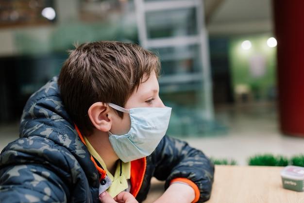 Junge mit medizinischer gesichtsmaske, schutzmaßnahmen gegen die ausbreitung von covid-19