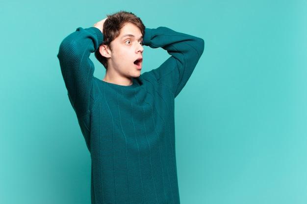 Junge mit offenem mund, der wegen eines schrecklichen fehlers entsetzt und schockiert aussieht und die hände zum kopf hebt