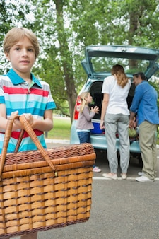 Junge mit picknickkorb während familie im hintergrund am autokofferraum