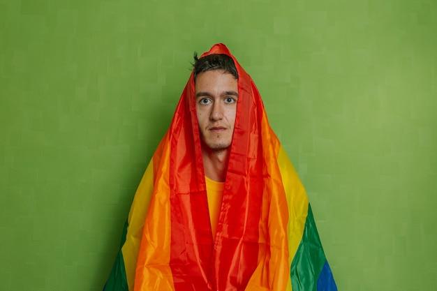 Junge mit regenbogenfahne auf seinem kopf auf grünem hintergrund. lgbti, schwul