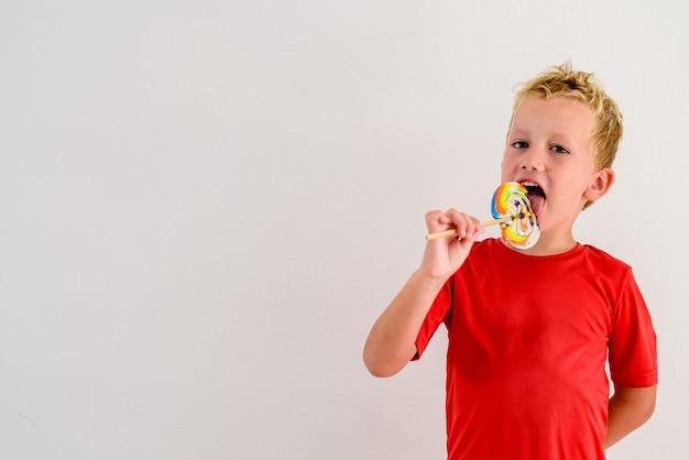 Junge mit rotem hemd auf dem weißen hintergrund, der einen bunten spaß und ein lachen eines lutschers isst.