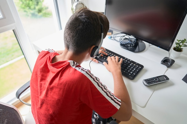 Junge mit rotem t-shirt im computer