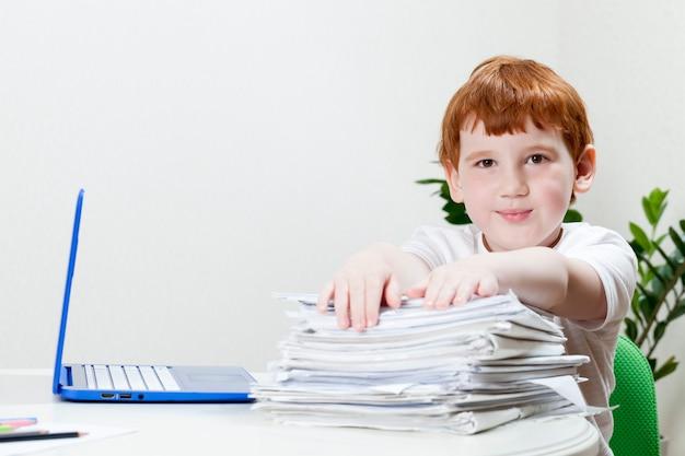 Junge mit roten haaren lernt aus der ferne über einen computer und sitzt mit einer großen anzahl von blättern papier