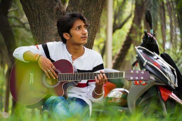 Junge mit roter gitarre mit rotem fahrrad