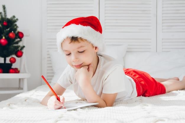 Junge mit roter mütze schreibt einen brief an den weihnachtsmann