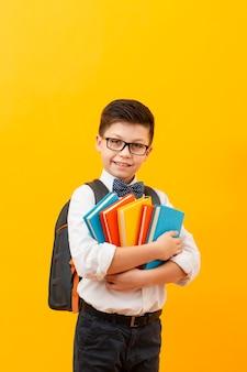 Junge mit rucksack, der stapel bücher hält