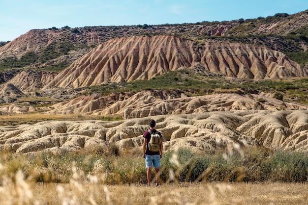 Junge mit rucksack und kurzen jeans, die in der wüstenlandschaft von bardenas reales navarra reisen