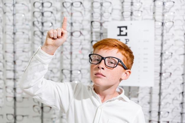 Junge mit schauspiel zeigend auf die aufwärts richtung, die gegen brillenanzeigenhintergrund steht