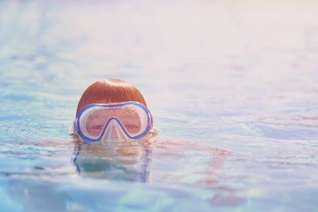 Junge mit schwimmbrille tauchen im schwimmbad