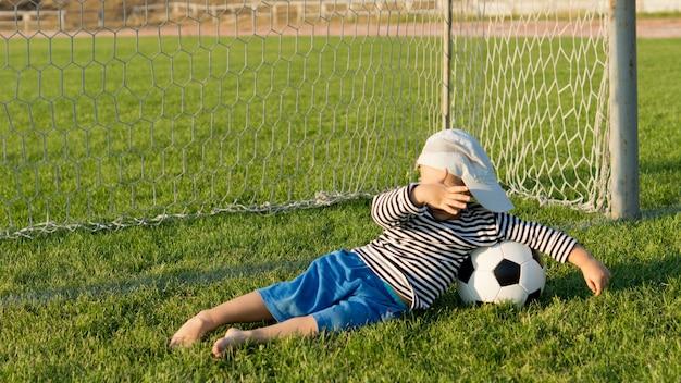 Junge mit seinem fußball, der barfuß auf dem gras in den toren liegt und seine augen gegen das leuchten der abendsonne abschirmt