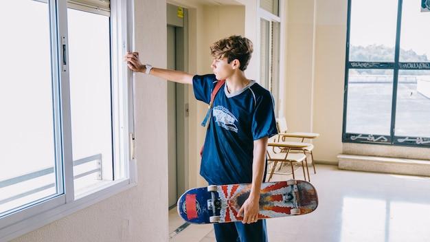 Junge mit skateboard blick durch fenster