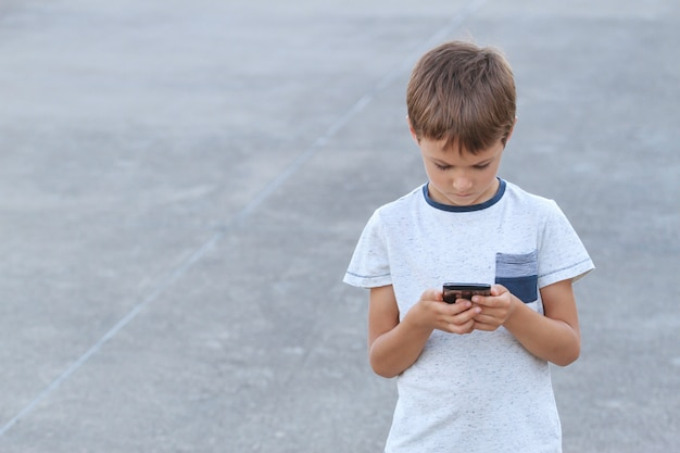 Junge mit smartphone-sms, spiel spielend, mit apps. grauer städtischer hintergrund. kindheit, technologie, freizeitkonzept