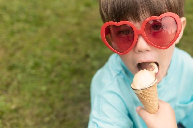 Junge mit sonnenbrille, die eis isst