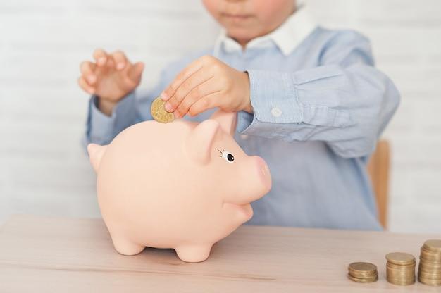 Junge mit sparschwein. kindheit, geld, investition und glückliche menschen konzept