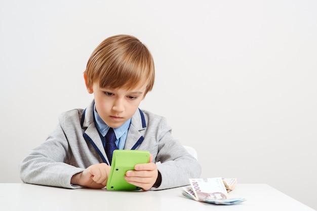 Junge mit taschenrechner zählt geld. zukünftige bildung.