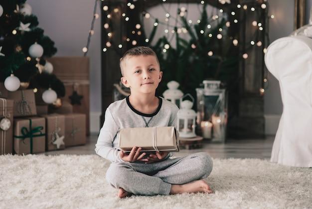 Junge mit weihnachtsgeschenk sitzt auf teppich