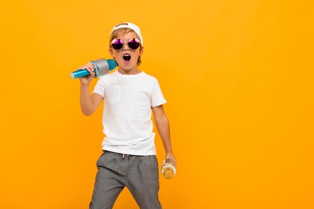 Junge mit zwei mikrofonen singt auf einer gelben hellen wand