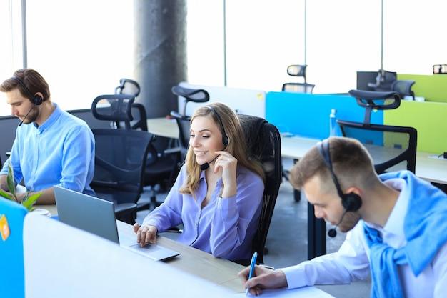 Junge mitarbeiterin arbeitet mit headset und wird von ihrem team begleitet