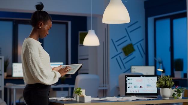 Junge mitarbeiterin, die spät in der nacht im büro steht und diagramme während der pause im geschäftsbüro analysiert