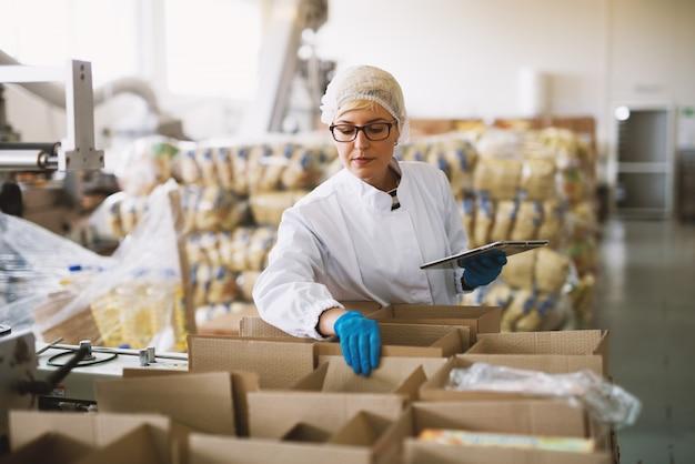 Junge mitarbeiterin in steriler kleidung überprüft pakete, die zur lieferung bereit sind.