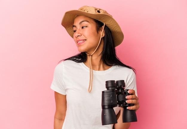 Junge mixed race explorer-frau, die ein fernglas einzeln auf rosafarbenem hintergrund hält, sieht beiseite lächelnd, fröhlich und angenehm aus.