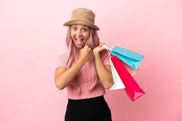 Junge mixed race frau mit einkaufstasche auf rosa hintergrund isoliert einen sieg feiernd