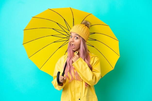 Junge mixed-race-frau mit regenfestem mantel und regenschirm, die einen sieg feiert