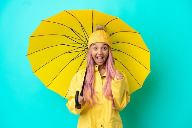 Junge mixed-race-frau mit regenfestem mantel und regenschirm, die einen sieg in siegerposition feiert