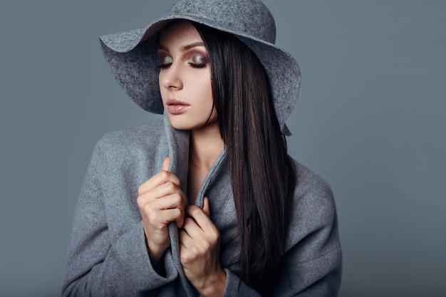 Junge mode brunette-frauenschönheit im grauen mantel und im hut